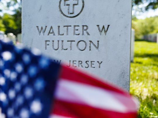 An American flag sits in front of a headstone in Arlington
