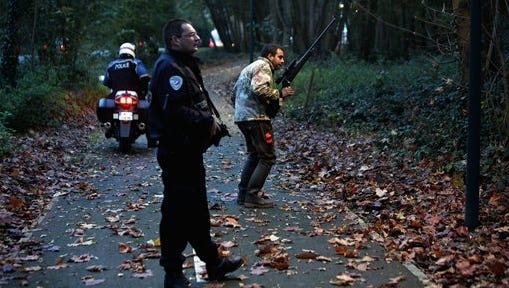 Members of the police animal brigade walk through a wood in Montevrain, east of Paris, Thursday. French authorities say a young tiger is on the loose near Disneyland Paris, one of Europe's top tourist destinations, and have urged residents in three towns to stay indoors.