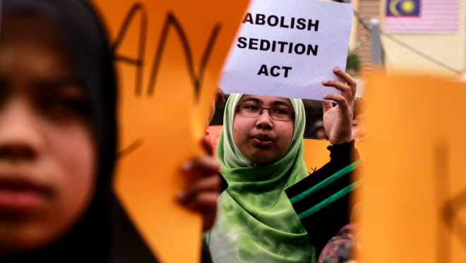 A Malaysian student holds a placard during a protest in solidarity for Malaysian law professor Azmi Sharom, at Malaya University in Kuala Lumpur, Malaysia, Sept. 9, 2014.ple - including a journalist for an online news portal - are being investigated under the act, which Prime Minister Najib Razak promised to abolish as part of his reform agenda. The 1948 act was implemented by British colonialists in a bid to stifle political dissent against its rule over the peninsula. The law criminalizes speech that could bring hatred or contempt or disaffection against the government. Conviction carries a maximum penalty of up to three years imprisonment or a fine of 5,000 ringgit (1,600 US dollar) or both. The government said the Sedition Act would be replaced by the National Harmony Bill, still under consultation, which is intended to be 'a comprehensive, fair and lasting piece of legislation that promotes national harmony. '  EPA/AZHAR RAHIM