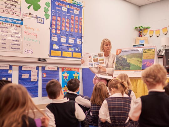 Teaching aide Eileen Thomas reads to a kindergarten