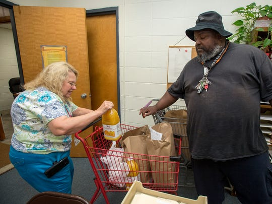 Melanie Carey, social services case worker at the Salvation Army in Salisbury, loads juice and other groceries into a cart for Salisbury resident Perry Banks.