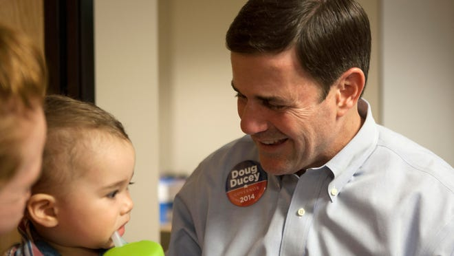 Doug Ducey, a former CEO of Cold Stone Creamery and a Republican candidate for Arizona governor, greets 1-year-old Kai Aguirre during an ice-cream-social campaign event on July 2.