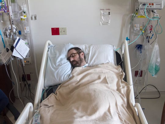 Jake Booth sleeps in his room at Promise Hospital in Fort Myers. Booth was in a coma for 42 days after getting pneumonia.