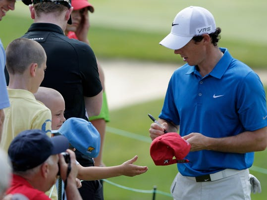 Rory McIllroy, of Northern Ireland, signs autographs for fans during the pro-am for the the Memorial golf tournament Wednesday, May 28, 2014, in Dublin, Ohio. (AP Photo/Jay LaPrete)