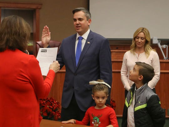 Newly-elected Redding City Council member Adam McElvain takes an oath Tuesday to join the council.