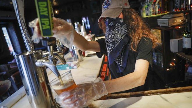 "In this June 22, 2020, file photo, a bartender pours a beer for a customer at Shade Bar NYC in New York. Authorities are closing honky tonks, bars and other drinking establishments in some parts of the U.S. to stem the surge of COVID-19 infections â€"" a move backed by sound science about risk factors that go beyond wearing or not wearing masks."
