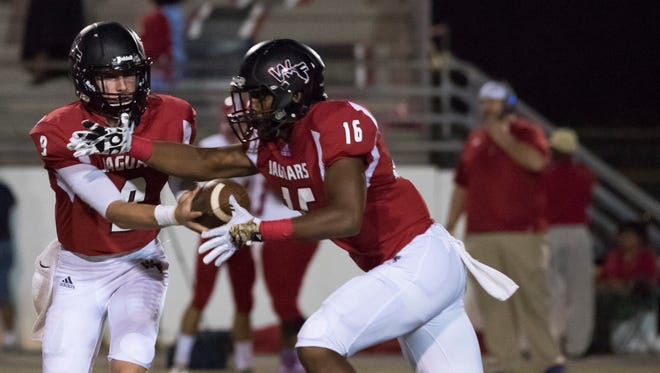 West Florida quarterback, Trevor Jordan, (No. 9) fakes the exchange with running back, Devin Abrams, (No. 16) during Friday night's game against Pine Forest.