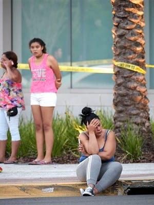 People wait outside the emergency entrance of the Orlando Regional Medical Center hospital after a shooting involving multiple fatalities at Pulse Orlando nightclub in Orlando, Fla., Sunday.