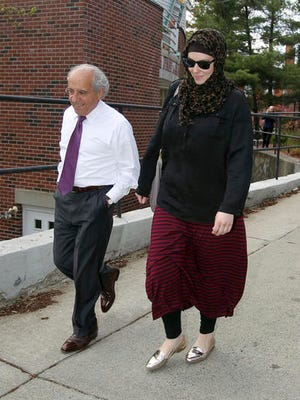 """File - In this April 29, 2013 file photo, Katherine Russell, right, widow of Boston Marathon bomber suspect Tamerlan Tsarnaev, leaves the law office of DeLuca and Weizenbaum with Amato DeLuca, left, in Providence, R.I. DeLuca says the new film """"Patriots Day"""" is unfair because it suggests Russell knew something was up before the attack and then didn't cooperate with the investigation afterward. Tamerlan Tsarnaev died during a violent encounter with police."""