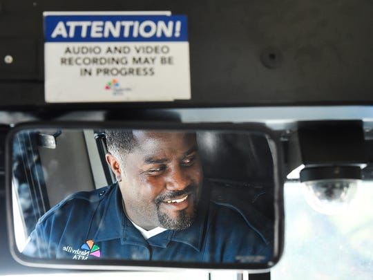 MTA driver Archie Harper smiles as he engages with ta rider boarding his bus.