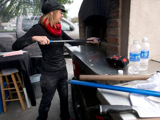 Cathy Saxton, mans the Rolling Embers, wood fired pizza oven during the first day of food truck operations at city hall Thursday. Under a new mayoral decree, food truck operations are now allowed on city hall property Thursday through Saturday from 8am-8p.m.