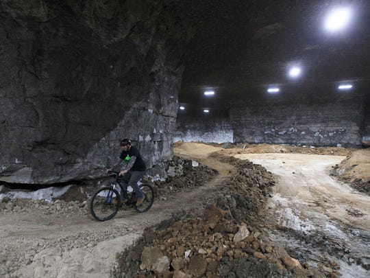 Joe Prisel, a course designer and builder, demonstrates one of the flatter trails that wind around a new course being built inside the Mega Caverns. November 25, 2014