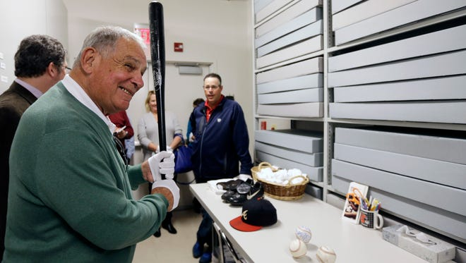 Former Atlanta Braves manager Bobby Cox holds the David Justice home run bat from Game 6 of the 1995 World Series during his orientation visit at the Baseball Hall of Fame on Monday, in Cooperstown. Former pitcher Greg Maddux, right, looks on. They will be inducted to the hall in July.