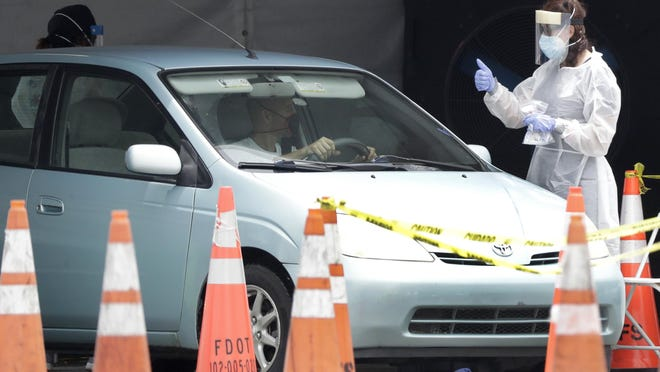 A healthcare worker gives a thumbs up to a driver as he stops his car on Wednesday at a COVID-19 testing site outside Hard Rock Stadium in Miami Gardens. Gov. Ron DeSantis quietly lifted travel restrictions Thursday on people coming to Florida from New York, New Jersey and Connecticut.
