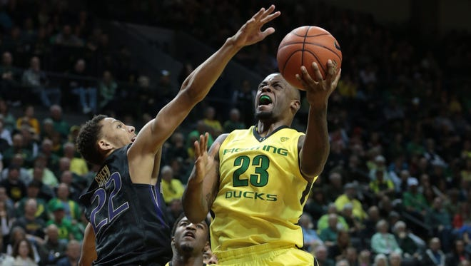Oregon forward Elgin Cook shoots against Washington forward Dominic Green in the second half at Matthew Knight Arena.