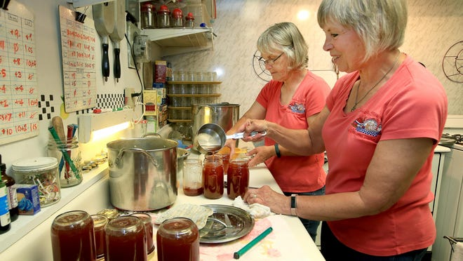 Kris Sallee, left, and Debbie Gerard make sandhill plum jelly at their industrial kitchen in Hutchinson as part of their Sticky Spoons jelly-making business Thursday afternoon. The two friends have been making jelly since 1994.