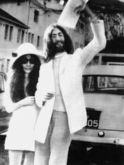John Lennon waves his marriage certificate with bride Yoko Ono after their wedding in Gibraltar on March 20, 1969.