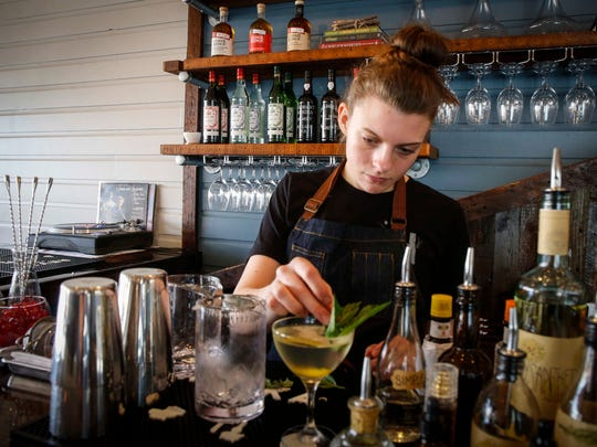 Rae Doyle, bar manager at Harbinger on Ingersoll Avenue in Des Moines, makes a basil and gin cocktail.