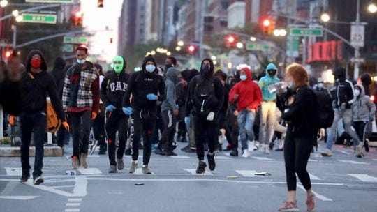 A group of young people walk south on Sixth Ave. in Manhattan June 1, 2020. Approximately one-hundred young people broke off from a march protesting the death of George Floyd and began vandalizing stores and property. A Verizon Store and a Foot Locker shoe store were among the stores looted.