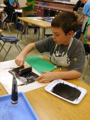 Students focus on rolling out their ink evenly on styrofam