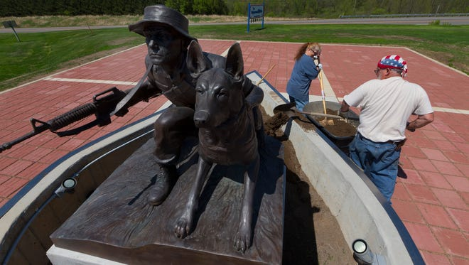 Volunteers Dan and Loretta Scheunemann perform landscaping work around a memorial dedicated to military dogs and their handlers at Highground Veterans Memorial Park outside of Neillsville. The memorial will be officially dedicated June 2.