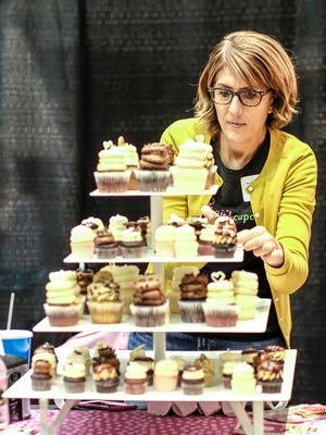 Gigi Farhat, owner of GiGi's Cupcakes works at filling and straightening her display of cupcakes at the Lansing Bridal Show World, January 8, 2017.