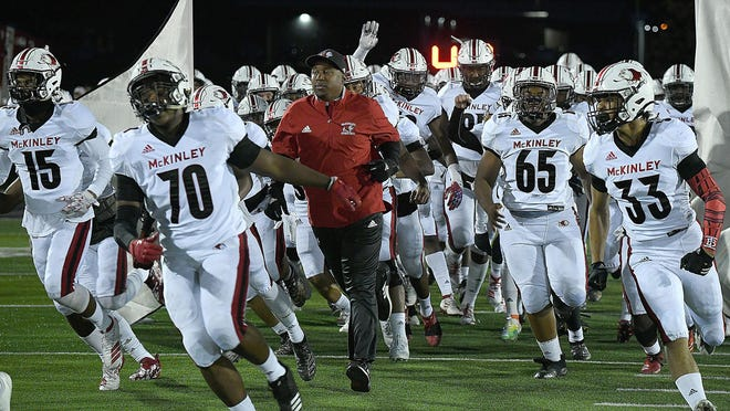 McKinley coach Marcus Wattley runs onto the field before a 2019 game against Perry.