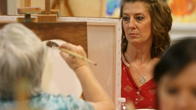 Breast cancer survivor and American Cancer Society volunteer Kim Gibson paints at The Ned in downtown Jackson on Tuesday.