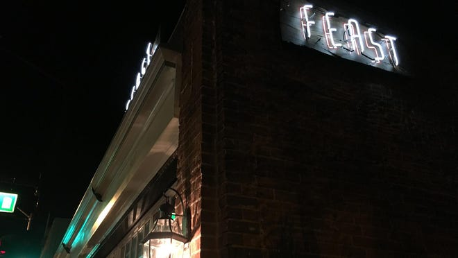 A night view of the exterior of Feast showing punches of neon signage. The restaurant occupies the old Jack Bacon building where South Virginia Street meets California Avenue.