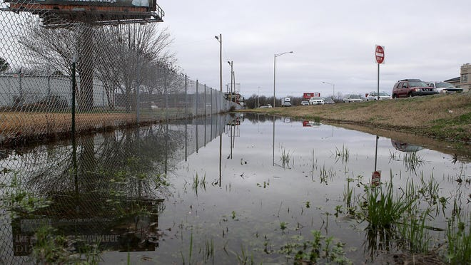 A flooded ditch is seen along the U.S. 45 Bypass, near State Street, on Tuesday.