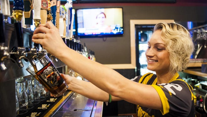 Autumn Bolyard pours a Mountain Man beer from The Front at Buffalo Wild Wings, which is participating in a statewide campaign for local beer.