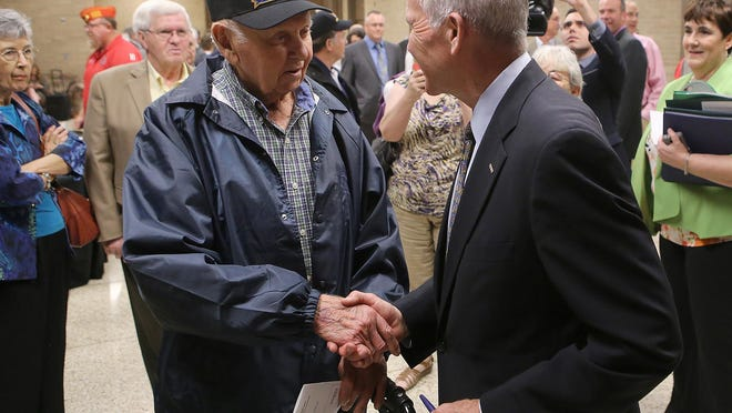 Retired Lt. Col. Oliver North, right, shakes hands with Joe McMurray after speaking Thursday during the Jackson State Foundation Banquet at the Carl Perkins Civic Center.