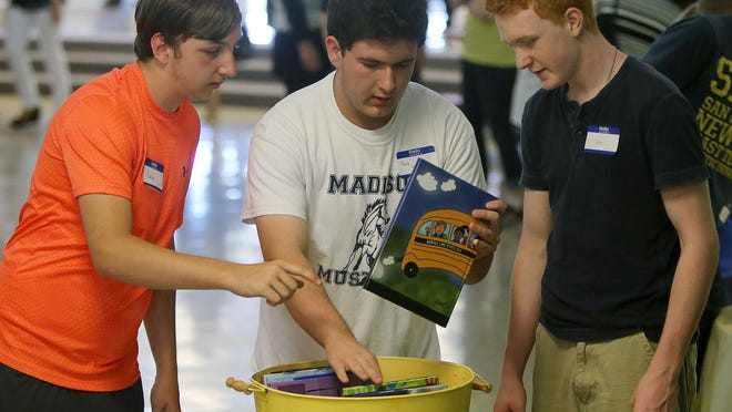 Keaton Metcalf, left, Jacob Gowan and Chase Moore search through yearbooks during a community farewell Saturday at Nova Elementary School.