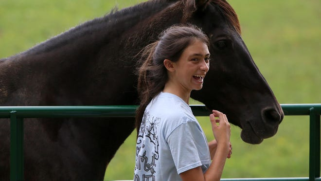 Maddie Jones smiles after petting a horse at Redemption Road Rescue on Saturday.