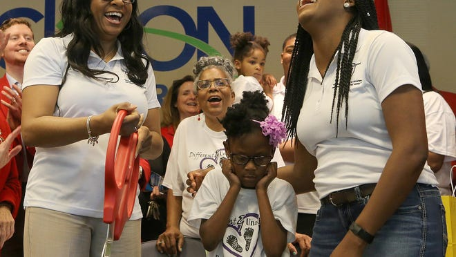 Different & Unashamed Executive Director Delita Johnson, left, Jayda Clark and Program Director Charity Thompson-Clark react after cutting the ribbon Wednesday during an event for out-of-town and home-based businesses at the Jackson Chamber.