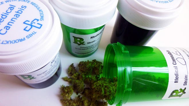 Close-up of four medical marijuana prescription containers. One opened container is in the foreground with cannabis bud falling out.