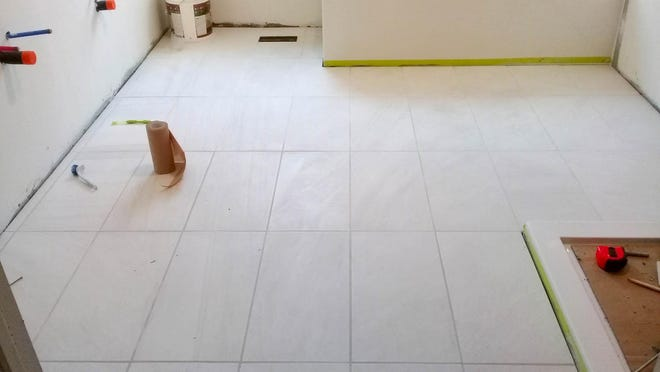 This bathroom tile floor was installed by a DIYer, who says his grout didn't turn out in the color he wanted.