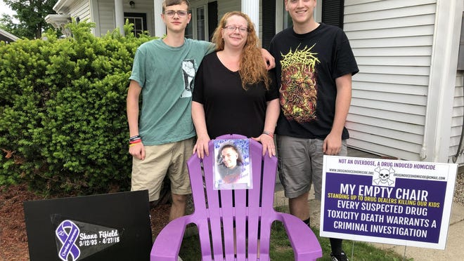 Kristen Fifield Roy stands with sons Adam Roy, left, and Matthew Roy at the site of Shane Fifield's Empty Chair which sits on their lawn on Lafayette Street in Rochester. The display aims to raise awareness about drug induced deaths. Shane died in 2018 of a fentanyl overdose.