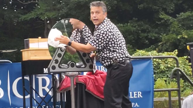 Magic Fred entertains children at one of the modified events of the Cocheco Arts Festival in Dover. The drive-in event was held in the parking lot of St. John's Methodist Church.