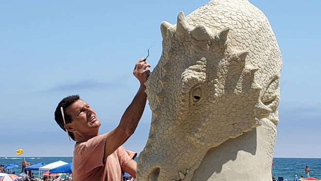 Hampton resident Greg Grady repairs a sand sculpture constructed by his son, Greg Jr., and Abe Waterman. The sculpture is to help remind people that the annual June Sand Sculpture competition will now happen Sept. 3-5. The event needed to be rescheduled due to COVID-19 health concerns.