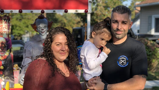 Bethany and Danny Hall and 3-year-old Cora in front of their Halloween display in Warwick.