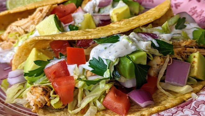 Chicken Tacos with shredded slow-cooked chicken, lettuce, tomato, avocado, red onion, cilantro and Lime Crema.