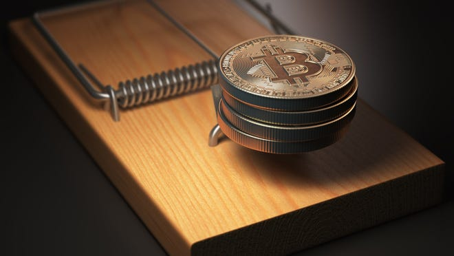 Physical bitcoin placed in a mouse trap.