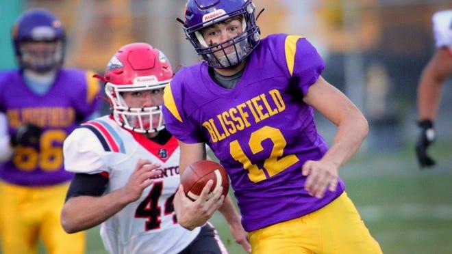 Blissfield quarterback Gavin Ganun (12) carries the ball ahead of Clinton's Brayden Randolph during their LCAA game on Friday night.