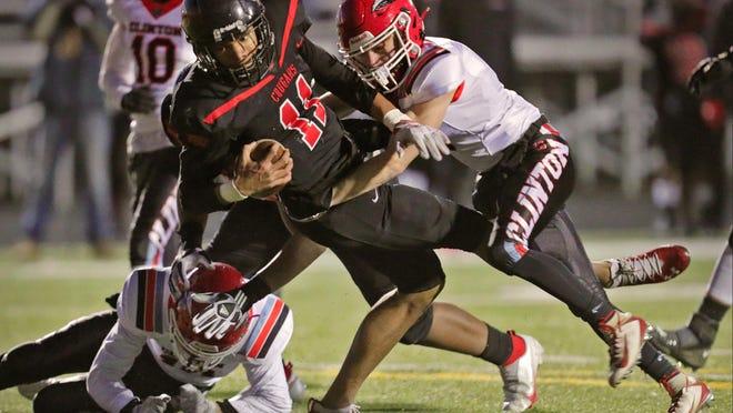 Clinton's Zak Shadley tackles Warren Michigan Collegiate quarterback Deion Black during Saturday's Division 6 regional final at Madison Heights Bishop Foley.
