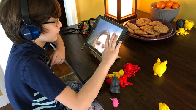 Ben Clevenger, a 12-year-old middle school student at J. Graham Brown School in Louisville, Kentucky, studies from home on April 7.