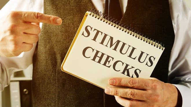 A man holding up and pointing to a sign that reads Stimulus Checks