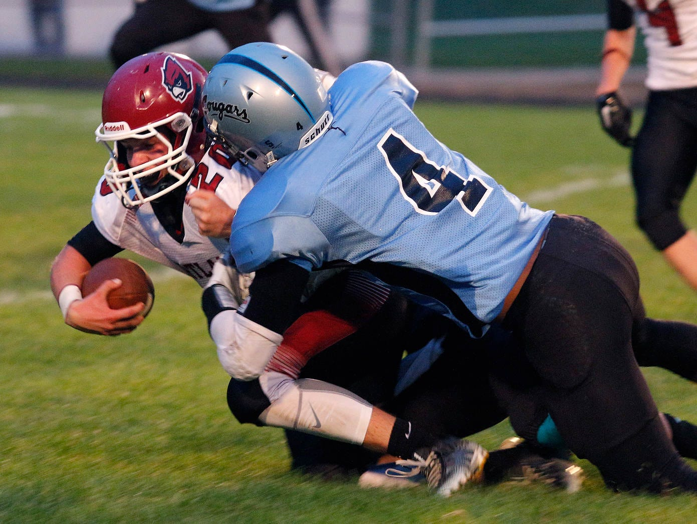 Portland'x Gabe Schrauben, left, is brought down by Lansing Catholic's Mitchell McInnis (4) Friday, Sept. 18, 2015, in Holt, Mich.