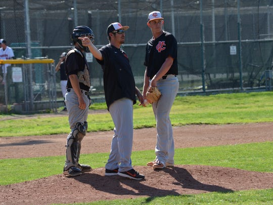 Pitching coach Jimmy Walker (middle), shown visiting the mound during the 2017 season, was hired as Ventura College baseball coach on Tuesday.
