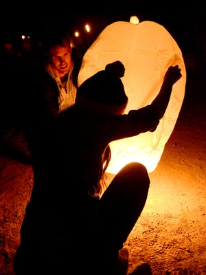 A couple light a lantern at a previous lantern festival in Fernley.